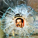 A portrait of Saddam Hussein lies behind a bullet hole in a shop window in Baghdad
