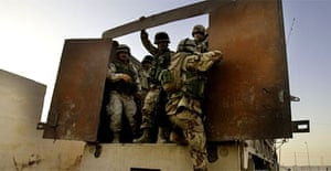 Iraqi soldiers load into the back of a truck in Ramadi. Photograph:  Jacob Silberberg/AP