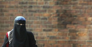 A Muslim woman wearing a Niqab walks in Blackburn, the constituency of MP Jack Straw