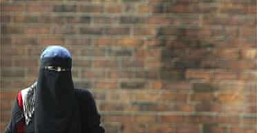 A Muslim woman wearing a Niqab walks in Blackburn, the constituency of MP Jack Straw