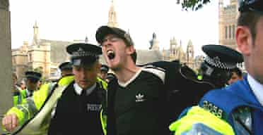 Police remove an anti-war protester from Parliament Square