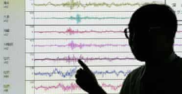 A member of staff at Japan's meteorological agency shows the point on a seismograph where North Korea's nuclear test was registered