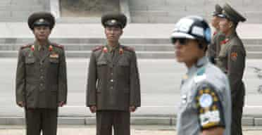 A South Korean soldier stands in front of North Korean troops at Panmunjom in the demilitarised zone separating the two countries