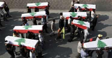 Mourners in Qana carry coffins draped in Lebanese flags. Photograph: Sean Smith/Guardian