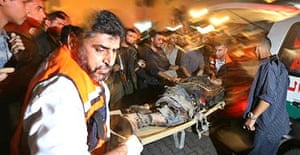 Palestinian doctors wheel the body of a militant killed during an Israeli operation in the Gaza Strip