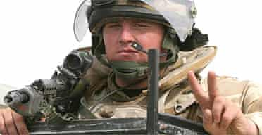A British soldier makes a V-sign at a checkpoint in Basra