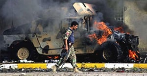 An Iraqi police commando walks by a burning humvee at the site of a suicide car bombing in the northern Iraqi oil hub of Kirkuk