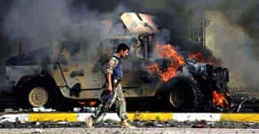 An Iraqi police commando walks by a burning humvee after a suicide bombing in Kirkuk