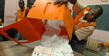 An election official empties a ballot box at the end of a day of voting in Kinshasa in the Democratic Republic of Congo
