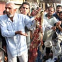 Iraqis hold up the bloodstained clothes of victims of a bomb attack on a market in the Shia Sadr City area of Baghdad