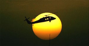 A US military helicopter flies over the heavily fortified Green Zone that houses the US Embassy and Iraqi government buildings at sunset.