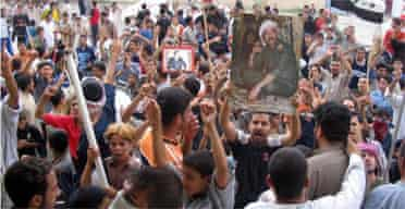 Iraqis hold flags and pictures of Saddam Hussein as they protest his death sentece verdict in his hometown of Tikrit