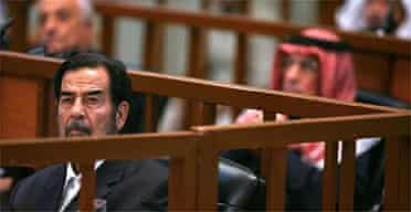 Saddam Hussein listens to testimony during his genocide trial in Baghdad. Photograph: Scott Nelson/AFP/Getty