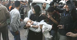 A Palestinian woman carries her injured son into the Beit Lahia hospital in the northern Gaza Strip