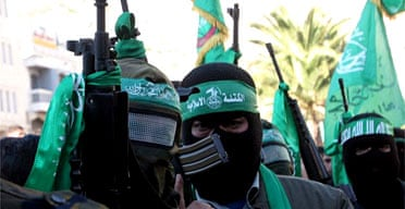 Hamas gunmen protest in the West Bank town of Nablus after 18 civilians were  killed by Israeli tank fire in Beit Hanoun