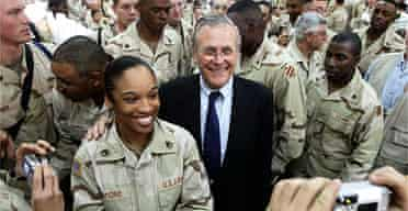 Donald Rumsfeld poses for photos with troops at an army camp in Baghdad in 2005. Photograph: Gerald Herbert/AP