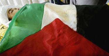 The body of three-year-old Maysa Athamna is covered with a Palestinian flag in preparation for her burial in the Gaza town of Beit Hanoun