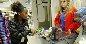 Hannah Pool removing packaging from groceries at a supermarket checkout