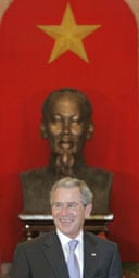 The US president, George Bush, stands in front of a bust of Ho Chi Minh at the presidential palace in Hanoi