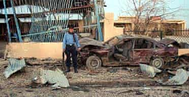 An Iraqi police officer inspects the scene of an explosion in Tal Afar, Iraq