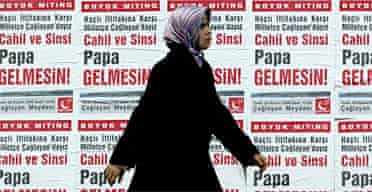 A woman walks past posters advertising an anti-pope rally in Istanbul