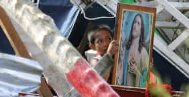 A boy salvages an image of Jesus from the ruins of his home on the main Philippines island of Luzon following typhoon Durian