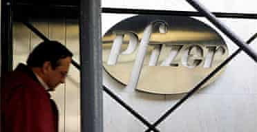 A pedestrian walks past the Pfizer Inc. headquarters building in New York