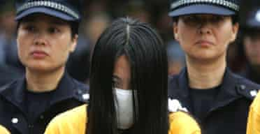 Chinese police escort a woman during a public shaming of people accused of involvement in prostitution in Shenzhen, Guangdong province