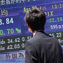 A Japanese businessman looks at the early morning stock figures on a NIkkei stock market screen in downtown Tokyo.