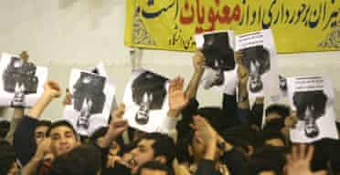 Iranian reformist students hold portraits of the country's president, Mahmoud Ahmadinejad, upside down in protest during his visit a Tehran university