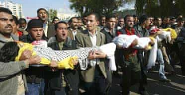 Mourners carry the bodies of Osama, nine, Ahmad, six, and Salam, three, who died together with their bodyguard while being driven to school in Gaza City