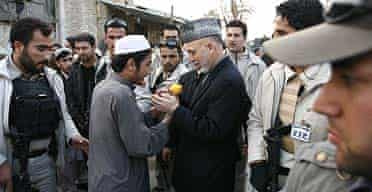 President Hamid Karzai walks the streets of Kandahar amid tight security following a spate of Taliban suicide bombings in the southern city