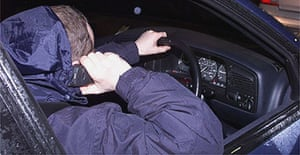 A motorist uses a hand-held mobile phone