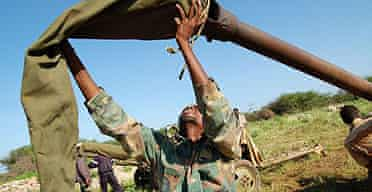 A Somali government soldier removes the cover of an artillery cannon in a training camp near Baidoa, Somalia.