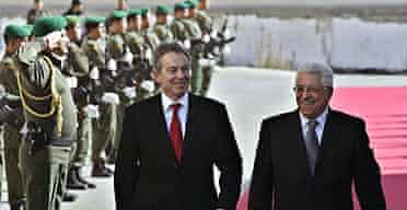Tony Blair and Palestinian president Mahmoud Abbas walk past an honour guard before a meeting in the West Bank town of Ramallah.