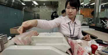 A bank teller counts Chinese yuan notes at a branch of the China Merchants Bank in Beijing.