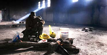 Samia, from Ghana, tends the fire in an abandoned factory that is home to about 80 of Rosarno's migrant workers