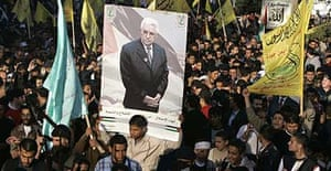 Supporters of the Fatah movement march with a poster of president Mahmoud Abbas
