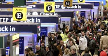 Passengers queue to check in at Heathrow airport