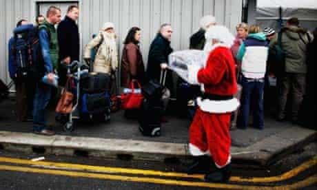 A man dressed as Santa Claus hands blankets to queueing passengers at Heathrow airport. Photograph: Daniel Berehulak/Getty