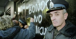 Police keep watch as people protest outside a bank in Buenos Aires, Argentina in 2002.
