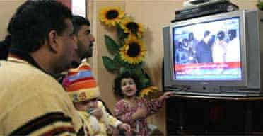 An Iraqi family watches television in their home in Basra, as Iraqi state TV transmits a video of the execution of former Iraqi president Saddam Hussein