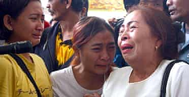 Distraught relatives of passengers await news from the scene of the Boeing 737 crash on Sulawesi island