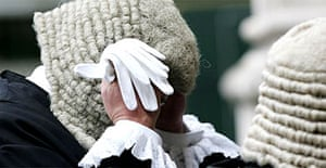A judge in ceremonial dress adjusts his wig