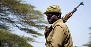 A Kenyan police officer patrols the country's border with Somalia, which Kenya has closed to try to keep out Islamist fighters