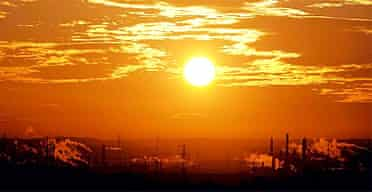 The sun rises over an industrial town