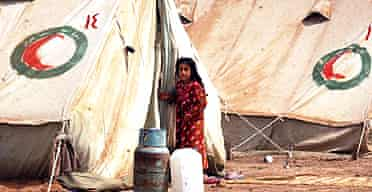 An Iraqi girl stands in front of her family's tent at a refugee camp in Diwaniya, south of Baghdad