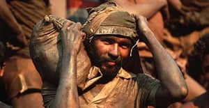 A Brazilian mineworker carries a sack of soil, which will be sifted for traces of gold