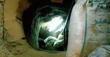 A smuggler enters a tunnel that runs from Gaza to Egypt