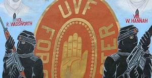 A boy walks past an Ulster Volunteer Force (UVF) mural on the Shankill Road in Belfast, Northern Ireland.